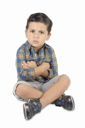 angry kid: angry child sitting on the floor. on white background Stock Photo