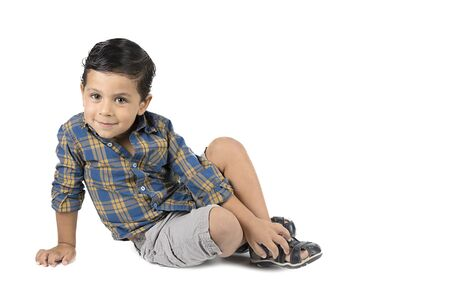 Cute little boy sitting isolated on white background. looking at camera photo