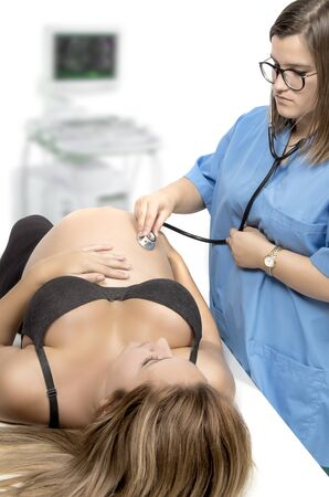 listening to heartbeat: Pregnant woman being examine by a doctor with a stethoscope