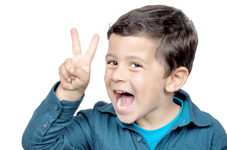 Portrait of little boy showing victory hand sign on white background photo