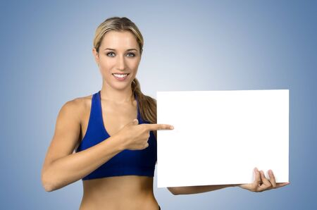hold on: Attractive positive young sportswoman holding blank board and pointing on it Stock Photo