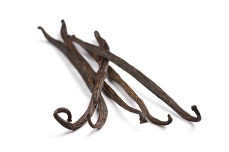 Five well dried vanilla beans on a white background
