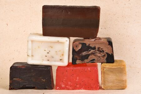 Bars of different colored handmade soap with herbs. photo