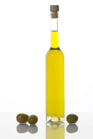 Bottle of olive oil and three olives isolated on white.