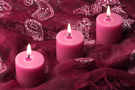 Three pink candles on a rich ornate purple cloth.