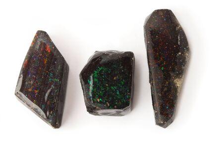 Three rough black matrix opals isolated on white, shallow dof. photo
