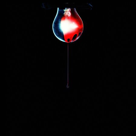 Old messy bulb covered with blood, isolated on black. photo