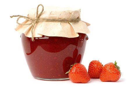 Homemade strawberry jam in a jar covered with paper, and three strawberries aside.
