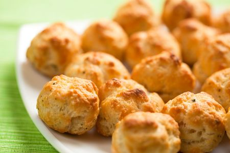 Gougeres, tiny French cheese buns, on a white plate.