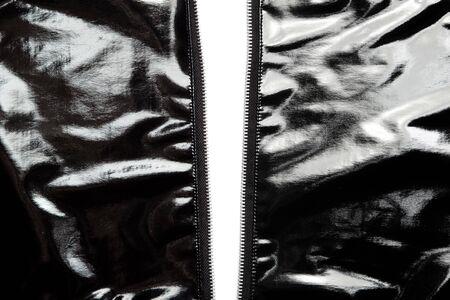 Two sides of black vinyl jacket unzipped. photo