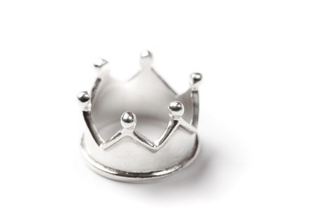 Tiny silver crown isolated on white, shallow dof. photo