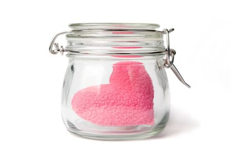 Pink plush heart in a jar, lid closed, isolated on white. photo