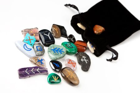 runes: Divination stones called Witches runes, scattering out of black velvet bag, isolated on white.