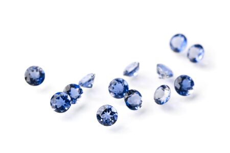Group of little faceted sapphires isolated on white. Focus is on the nearest gem.