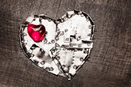 Metal armored heart and red glass heart on it. photo