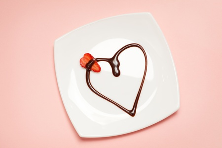 Valentines day dessert - heart made of chocolate topping and a slice of strawberry, view from above. photo