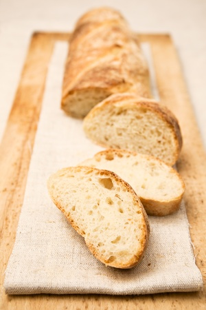 Homemade baguette, a French crusty long bread, with slices apart. photo
