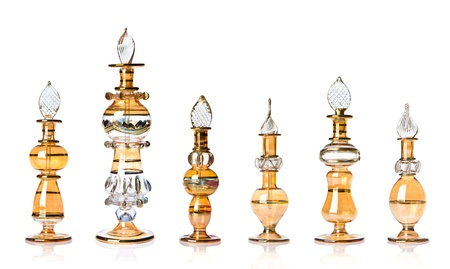Row of yellow-golden oriental perfume bottles isolated on white. Stock Photo