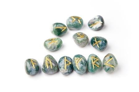 futhark: Golden runes carved on blue-green stones, six are forming classical Futhark order. Stock Photo