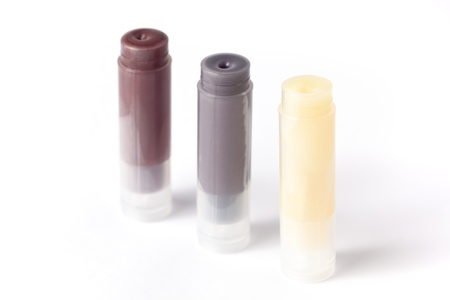 Three sticks of homemade lip balm, isolated on white.