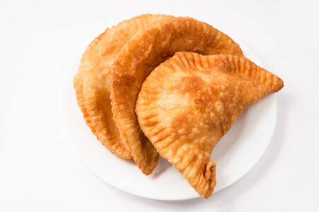Cheese empanada, meat empanada or chicken empanada on a white plate.  Empanada (meat pie) - traditional snack originally from Spain. Stock Photo