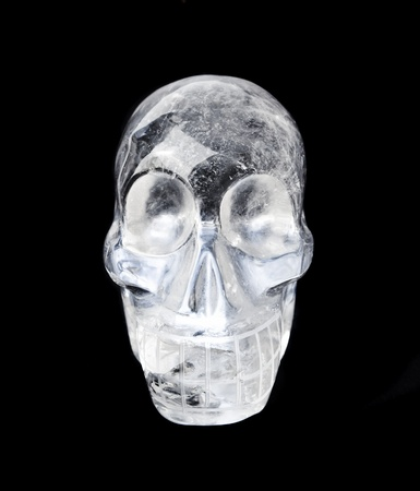 Traditional Central American quartz crystal carved skull, isolated on black.