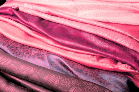 Pink silk fabric from India in a stack.