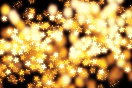 Glowing golden Christmas stars and lights on black background.