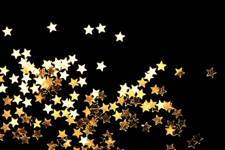 Golden Christmas stars on black background. Stock Photo