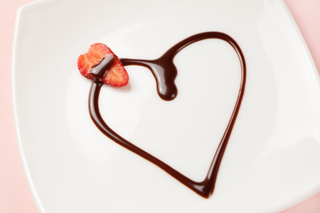 Close-up of a heart made of chocolate topping and a slice of strawberry on a white plate.  photo