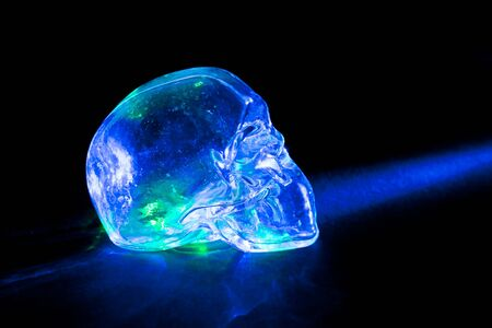 Transparent glass skull with blue and green light rays against black background. photo