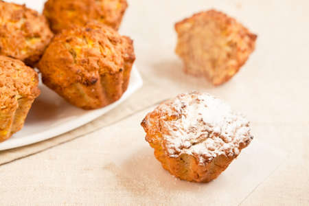 Fresh baked pumkin muffins with one aside and sugar icing sprinkling on it. photo