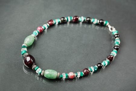 aventurine: Handmade natural gemstones (garnet, aventurine, malachite, tourmaline, quartz) bead necklace, shallow dof. Stock Photo