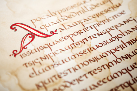 Calligraphic handwritten excerpt from Bible on a grunge paper, shallow dof. Archivio Fotografico