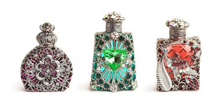 richly: Three richly ornate antique perfume bottles isolated on white.