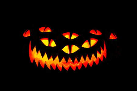 Traditional glowing Halloween Jack-o-Lantern face with carved unusual scary face with lots of eyes. Halloween pumpkin face isolated over black. Stock Photo - 48095060