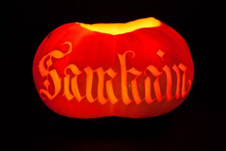 samhain: Traditional glowing Samhain Jack-o-Lantern with carved word Samhain on it. Pagan Wiccan Wheel of the Year holiday celebration. Stock Photo