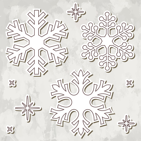 fiambres: Papel cortado copos de nieve sobre fondo gris texturizado.