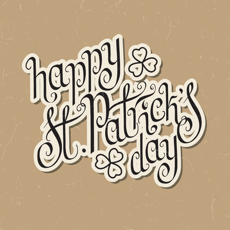 hand written: Paper cut hand written St. Patricks day greetings over textured vintage brown background.