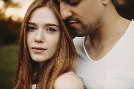 Ritratto ravvicinato di una bella donna dai capelli rossi che guarda l'obbiettivo mentre il suo ragazzo la abbraccia con gli occhi chiusi vicino al suo viso contro il tramonto mentre si frequenta.