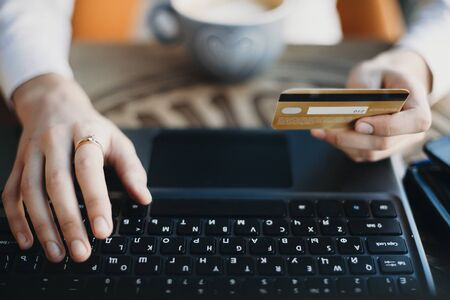 Close up hands holding a plastic gold credit card and using laptop. Online shopping concept.