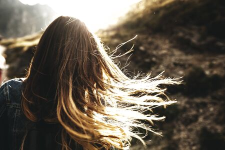 Unrecognizable back view of a female long hair brown playing in the sun flares in the morning against sun. Фото со стока