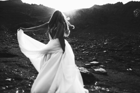 Back view of a unrecognizable bride dancing in the mountains against sunrise. Stock Photo