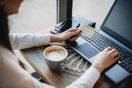 Side view of female hands holding a plastic gold credit card and using a laptop while sitting in a coffee shop . Online banking concept. Online shopping concept.