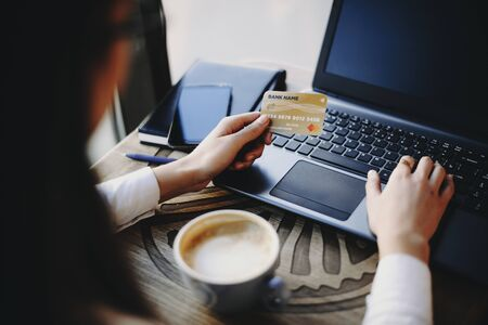 Female hand using a plastic credit card and a laptop for online transaction while drinking a coffee in a coffee shop.