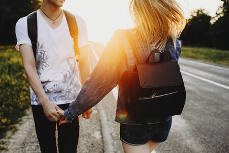Crop view of back of a young couple traveling to new places with backpacks and dancing against sunrise holding hands.