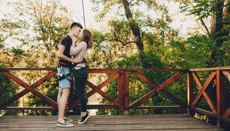 Two caucasian lovers kissing each other before getting a big portion of positive emotions on a tyrolean traverse Zdjęcie Seryjne