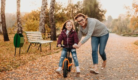 A cheerful young mother who is teaching her small and smiling daughter to ride the bike in a sunny autumn evening
