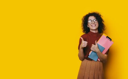 Lovely curly haired student holding some books is recommending something by posing on a yellow blank spaced background and showing the approbation sign