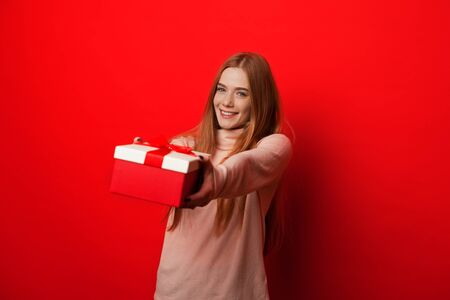 Cheerful caucasian girl with red hair and freckles is holding a present while posing on a red background